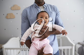 Close Up Of Father Holding Baby Daughter In Nursery