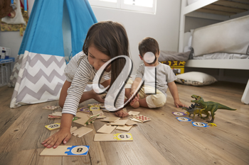 Two Children Playing Number Puzzle Game Together In Playroom