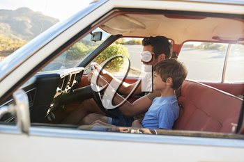 Father And Son In Front Seat Of Car On Road Trip