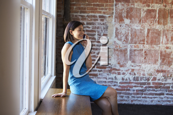 Businesswoman In Office Sitting By Window Using Mobile Phone