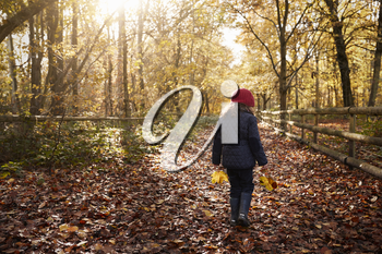 Young Girl Walking Along Path Through Autumn Countryside