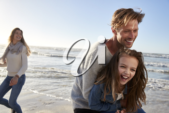 Parents With Daughter Having Fun On Winter Beach Together