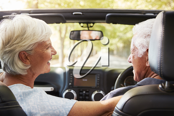 Senior Couple Drive Open Top Car On Countryside Road Trip