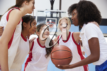 Female High School Basketball Players In Huddle Having Team Talk With Coach