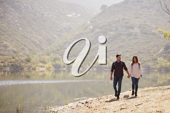 Young couple walk holding hands by a mountain lake