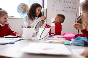 Smiling millennial female infant school teacher sitting at table with kids in a classroom giving pencils to a schoolboy, low angle