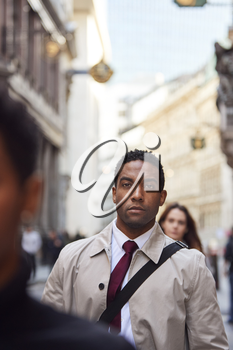 Young black businessman walking in a busy London street looking ahead, close up, vertical