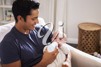 Smiling Hispanic father holding his four month old son feeds him a bottle at home, close up