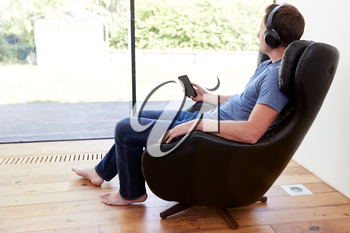 Man Relaxing In Chair At Home Streaming Music From Mobile Phone To Wireless Earphones