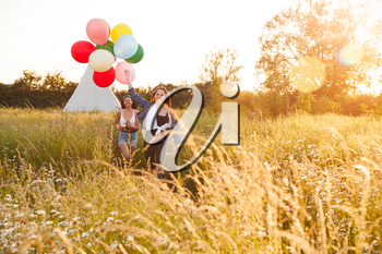 Portrait Of Two Female Friends Camping At Music Festival Running Through Field With Balloons