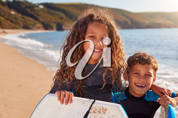 Portrait Of Children Wearing Wetsuits Holding Bodyboards On Summer Beach Vacation Having Fun By Sea