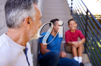 Smiling Multi-Generation Male Hispanic Family Sitting On Steps In Garden And Talking Together