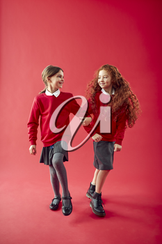 Two Elementary School Pupils Wearing Uniform Linking Arms Against Red Studio Background