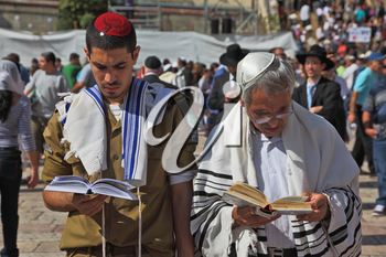 Jerusalem - October 16: The Holy Western Wall of the Temple. Jewish family - the father of religious clothing and his son, a soldier in uniform, praying in the square near the Wailing Wall in Sukkot,