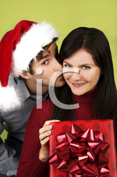 Royalty Free Photo of a Man Kissing a Woman With a Present