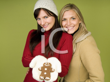 Royalty Free Photo of Two Women in Winter Clothing, One Holding a Gingerbread Man