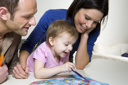 Royalty Free Photo of a Couple Helping Their Daughter With an Activity Book