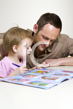 Royalty Free Photo of a Father Helping His Child With an Activity Book