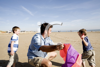 Royalty Free Photo of a Father and Sons Getting Ready to Fly a Kite on the Beach
