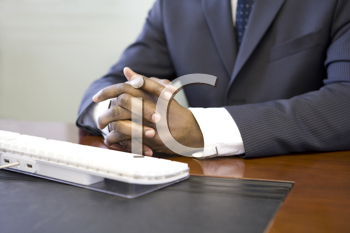 Royalty Free Photo of Clasped Hands Beside a Keyboard