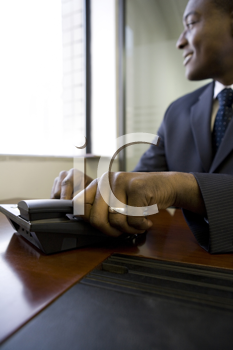 Royalty Free Photo of a Black Businessman Answering the Telephone