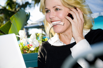 Royalty Free Photo of a Woman With a Laptop Talking on a Telephone