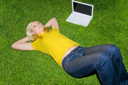 Royalty Free Photo of a Girl Lying on the Grass Beside a Laptop