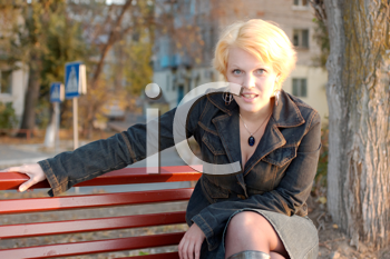 Beautiful girl on a park bench alone