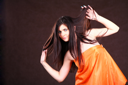 Attractive girl in orange fabric studio shot over brown background