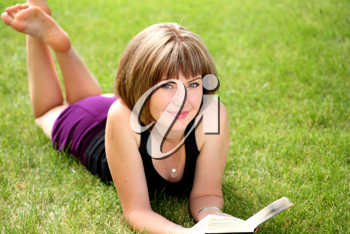 Portrait of beautiful relaxed young female student with a book