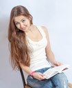 Closeup portrait of a young smiling woman sitting on a chair in jeans reading a book