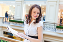 brunette holding book in her hands and looking at camera