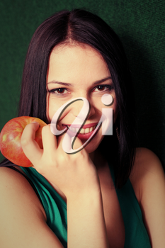 women with apple near face smiling