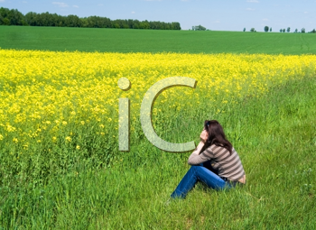 Royalty Free Photo of a Woman Sitting in a Field