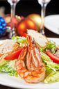 Tasty shrimp salad with vegetables on christmas table