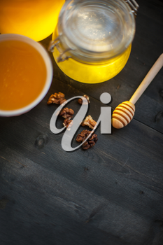 Honey with walnut on wooden background
