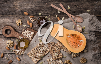 Pumpkin, nuts,  honey and seeds on wooden table. Rustic style