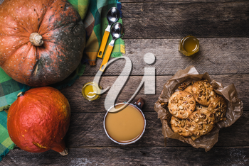 Pumpkins, soup, honey and cookies with nuts on wood. Autumn Season food photo