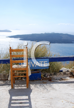 Royalty Free Photo of a Chair Overlooking the Caldera in Santorini