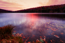 Fall landscape with the forest lake at sunset.