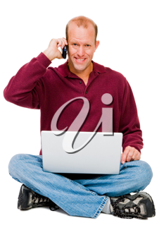 Royalty Free Photo of a Man Sitting Down Talking on his Cellular Phone and Holding a Laptop