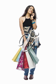 Young woman holding shopping bags and talking on a mobile phone