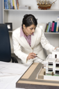Businesswoman looking at a model home in an office