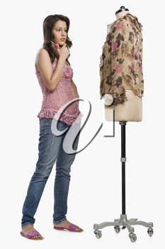 Female fashion designer standing near a mannequin and thinking