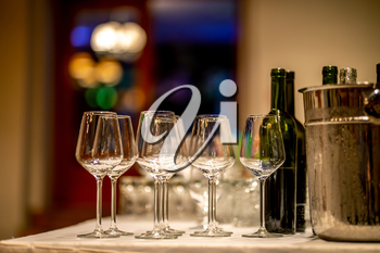 Empty glasses, wine bottles and bucket with ice on table in restaurant. Ice bucket, wine glasses and bottles arranged on the table for wedding reception.