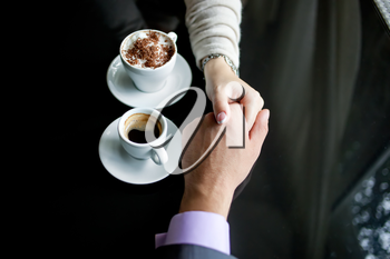 Royalty Free Photo of a Couple Holding Hands While Having Coffee