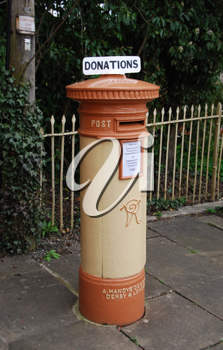 Royalty Free Photo of an Orange and Vintage British Postbox on the Sidewalk