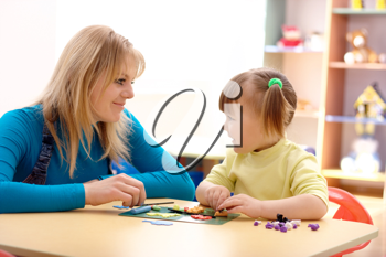 Royalty Free Photo of a Teacher and a Little Girl Playing With Plasticine