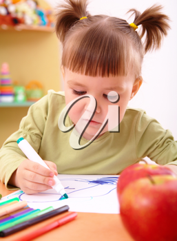 Royalty Free Photo of a Little Girl Colouring With a Marker and an Apple in Front of Her