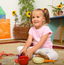 Royalty Free Photo of a Little Girl Playing on the Floor